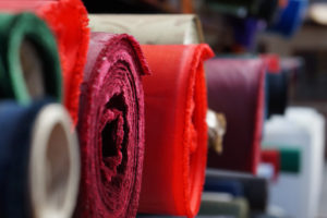 Rolls of different colored textile material on a warehouse shelf used for upholstery services