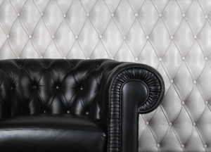 A classic styled black leather armchair , a durable upholstery fabric.
