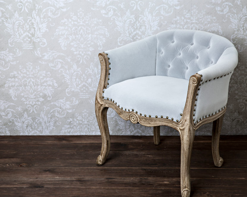 Custom vintage upholstery chair with a beautiful wall paper backdrop.