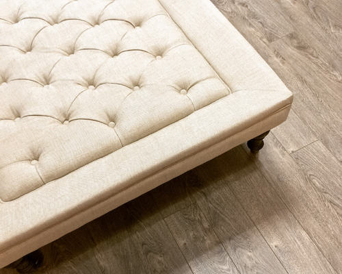 Fancy ottoman on wooden floor with linen fabric used for upholstery.